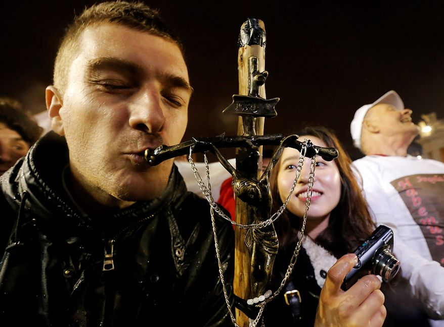 A pilgrim kisses a cross after white smoke billowed from the chimney on the Sistine Chapel indicating that a new pope has been elected in St. Peter's Square at the Vatican, Wednesday, March 13, 2013. (AP Photo/Dmitry Lovetsky)