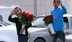 """Two Syrian brothers Bashar, 12, left, and Rasem, 14, right, who fled their home from Hassakeh, try to sell flowers to make a living in Beirut, Lebanon, Wednesday, March 13, 2013. Save the Children, which is providing humanitarian and relief in Syria and neighboring countries, called on all groups taking part in the conflict to allow unfettered, safe access to populations in need and to """"ensure that everything is done to bring the fighting to an end."""" (AP Photo/Bilal Hussein)"""