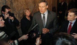 Standing in the wings of the Washington State House Chamber in Olympia,Wash., Monday, March 11, 2013 with Rep. Jamie Pedersen, D-43rd Dist., right, Gov. Jay Inslee speaks to reporters regarding possible legislation regarding possible future firearms regulation. (AP Photo/The Olympian, Steve Bloom)
