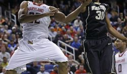 Maryland's Dez Wells (32) shoots as Wake Forest's Travis McKie (30) defends during the first half of an NCAA college basketball game at the Atlantic Coast Conference men's tournament in Greensboro, N.C., Thursday, March 14, 2013. (AP Photo/Gerry Broome)