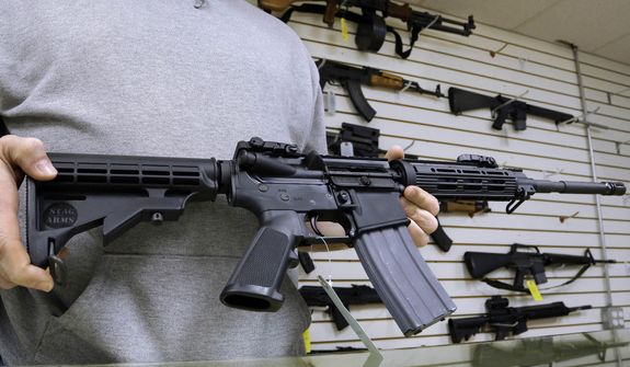 John Jackson, co-owner of Capitol City Arms Supply, shows an AR-15 assault rifle for sale at his business in Springfield, Ill., on  Jan. 16, 2013. (Associated Press) **FILE**
