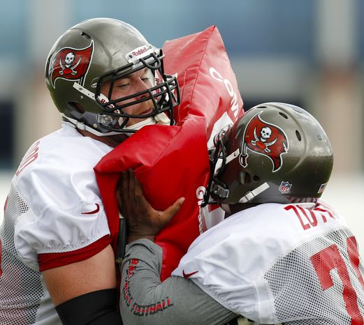 **FILE** Tampa Bay Buccaneers offensive linemen Jeremy Trueblood, left, and Jeremy Zuttah participate in a blocking drill during a workout at NFL football training camp, Saturday, July 28, 2012, in Tampa, Fla. (AP Photo/Mike Carlson)