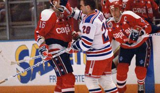 **FILE** New York Rangers Tie Domi (28) shoves his glove in the face of Washington Capitals Alan May after the two exchanged words during the first period of their game at New York's Madison Square Garden, Nov. 11, 1992. (AP Photo/Ron Frehm)