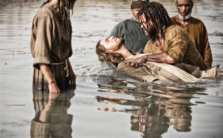 "Diogo Morgado as Jesus, center, is baptized by Daniel Percival, as John, in a scene from History's ""The Bible.""  The five-part mini-series, produced by the husband-and-wife team of Mark Burnett and Roma Dow"