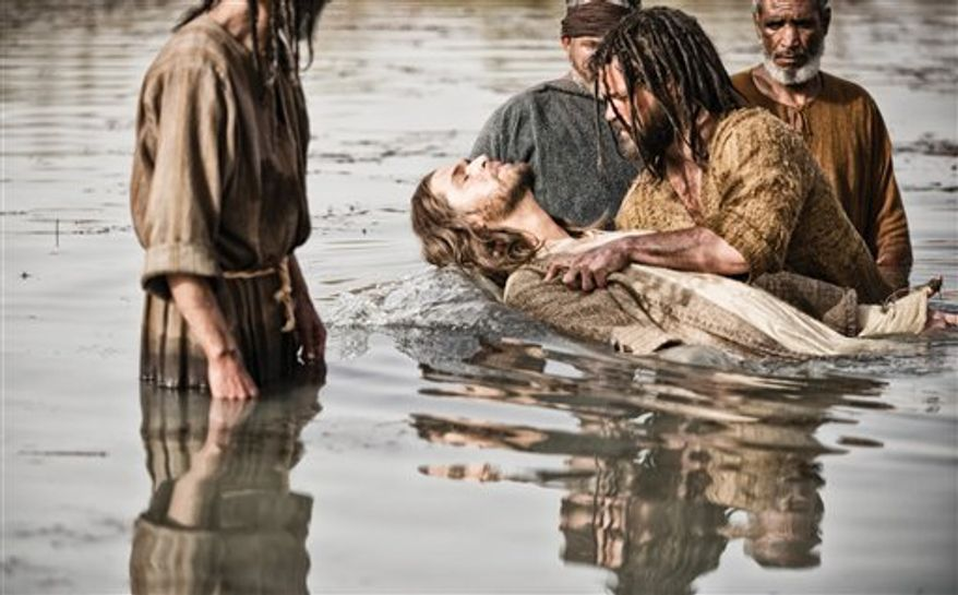 """Diogo Morgado as Jesus, center, is baptized by Daniel Percival, as John, in a scene from History's """"The Bible.""""  The five-part mini-series, produced by the husband-and-wife team of Mark Burnett and Roma Downey, concluded March, 31. The producers now plan on bringing the story to the big screen. (AP Photo/History, Joe Alblas)"""