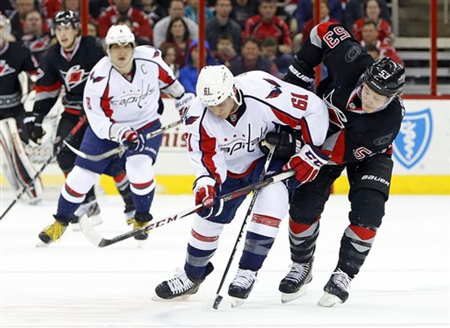 Carolina Hurricanes' Jeff Skinner (53) battles with Washington Capitals' Steven Oleksy (61) during the second period of an NHL hockey game on Thursday, March 14, 2013, in Raleigh, N.C. (AP Photo/Karl B DeBlaker)