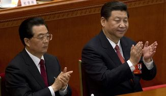 Former Chinese President Hu Jintao, left, and newly named President Xi Jinping clap during a plenary session of the National People's Congress held in Beijing's Great Hall of the People, in China, Thursday, March 14, 2013. (AP Photo/Alexander F. Yuan)
