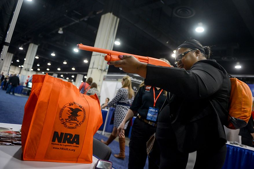 Sierra Baker of Murfreesboro, Tenn. plays a shooting game at a National Rifle Association booth in the downstairs exhibition hall at this year's Conservative Political Action Conference (C.P.A.C.) held at the Gaylord National Hotel, National Harbor, Md., Thursday, March 14, 2013. (Andrew Harnik/The Washington Times)