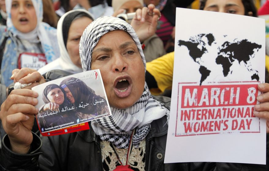 "An Egyptian woman shouts anti-Muslim Brotherhood slogans during a demonstration in Cairo on Friday, March 8, 2013, marking International Women's Day. The Arabic reads, ""Bread, freedom, social justice."" (AP Photo/Amr Nabil)"