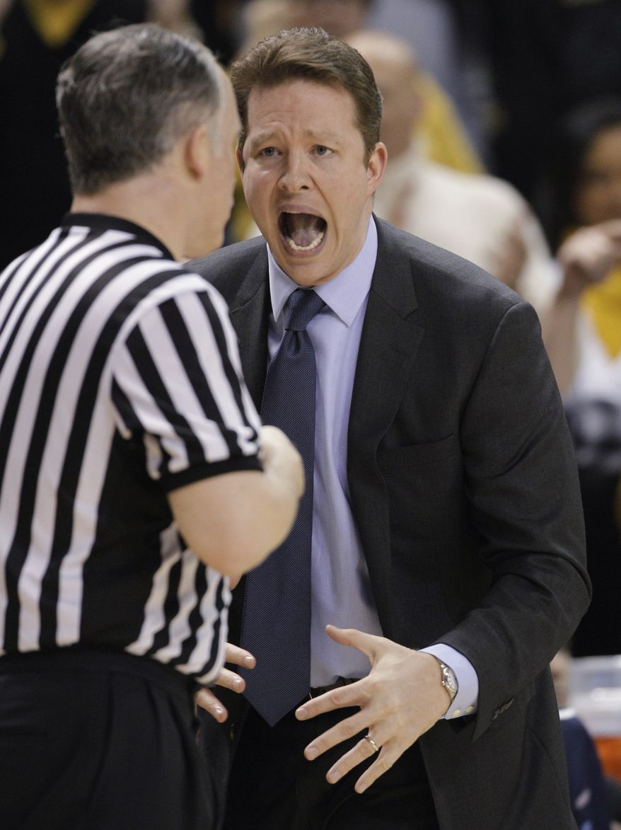**FILE** Richmond coach Chris Mooney disputes a call during the first half of an NCAA college basketball game against Virginia Commonwealth in Richmond, Va., Wednesday, March 6, 2013. (AP Photo/Steve Helber)