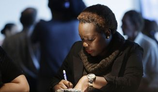 An unidentified woman answers questions on a job application at a job fair in Sunrise, Fla., on Tuesday, Jan. 22, 2013. (AP Photo/J. Pat Carter)
