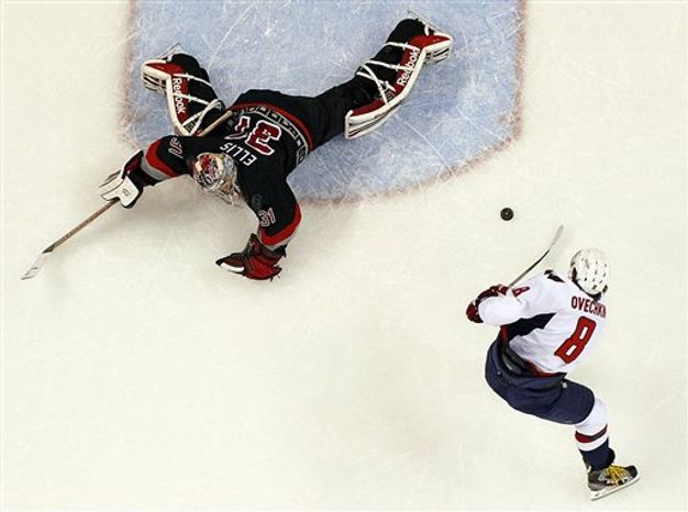 Carolina Hurricanes goalie Dan Ellis (31) stretches out to block the shot of Washington Capitals' Alex Ovechkin (8), of Russia, during the third period of an NHL hockey game on Thursday, March 14, 2013, in Raleigh, N.C. The Capitals won 3-2. (AP Photo/Karl B DeBlaker)