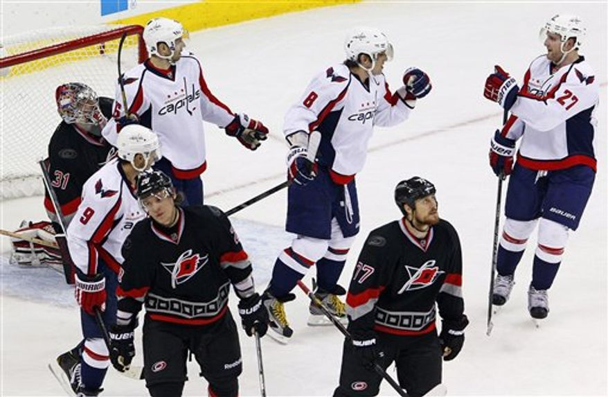 Washington Capitals' Alex Ovechkin (8), of Russia, celebrates a goal by teammate Mike Ribeiro (9) with Karl Alzner (27) and Eric Fehr (16) in front of Carolina Hurricanes goalie Dan Ellis (31) near Hurricanes' Alexander Semin (28), also of Russia, and Joe Corvo (77) during the third period of an NHL hockey game on Thursday, March 14, 2013, in Raleigh, N.C. The Capitals won 3-2. (AP Photo/Karl B DeBlaker)