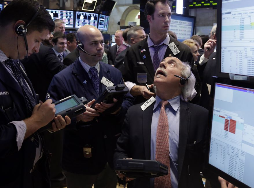 Peter Tuchman (right) works with fellow traders on the floor of the New York Stock Exchange on March 15, 2013. (Associated Press)