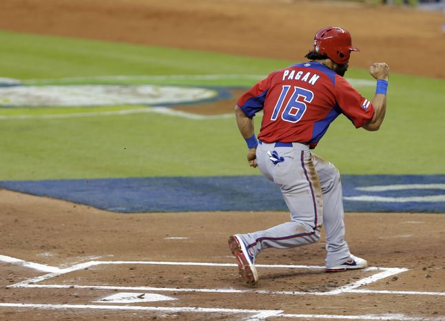 Puerto Rico's Angel Pagan celebrates as he scores on an RBI single by Mike Aviles during the first inning of a second round elimination game at the World Baseball Classic against the United States, Friday, March 15, 2013 in Miami. (AP Photo/Wilfredo Lee)