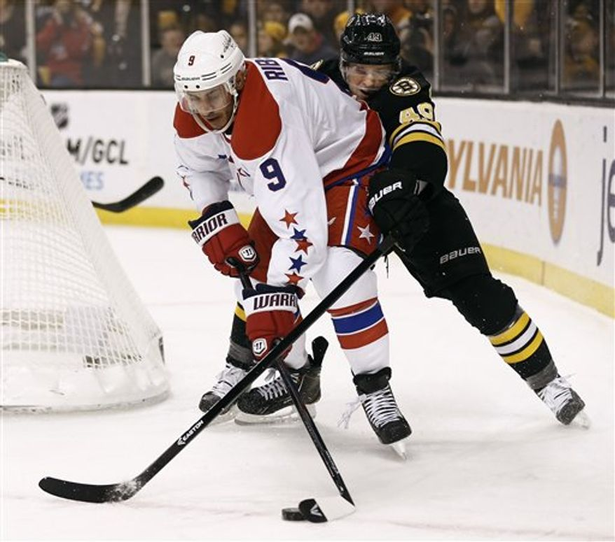 Washington Capitals' Mike Ribeiro (9) tries to keep the puck away from Boston Bruins' Rich Peverley during the first period of a NHL hockey game in Boston Saturday, March 16, 2013. (AP Photo/Winslow Townson)