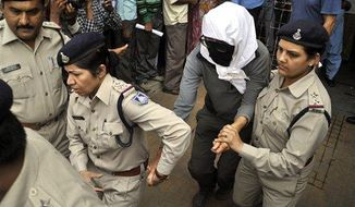 A Swiss woman, center, who was gang raped by a group of eight men while touring by bicycle with her husband, is escorted by policewomen for a medical examination at a hospital in Gwalior, in the central Indian state of Madhya Pradesh, Saturday, March 16, 2013. Thirteen men were detained and questioned in connection with the attack. (Associated Press)