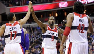 Washington Wizards forward Martell Webster (9) reacts with teammates Garrett Temple (17) and Nene (42), of Brazil, during the second half of an NBA basketball game against the Phoenix Suns, Saturday, March 16, 2013, in Washington. The Wizards won 127-105. (AP Photo/Nick Wass)