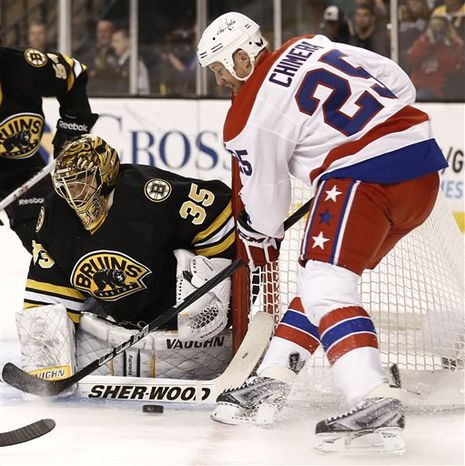 Boston Bruins goalie Anton Khudobin, left, of Russia, stops Washington Capitals' Jason Chimera during the first period of a NHL hockey game in Boston Saturday, March 16, 2013. (AP Photo/Winslow Townson)