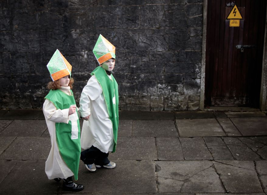 Children dressed as Ireland's patron saint make their way to the St. Patrick's Day parade during celebrations in Limerick, Ireland, on Sunday, March 17, 2013. (AP Photo/Peter Morrison)