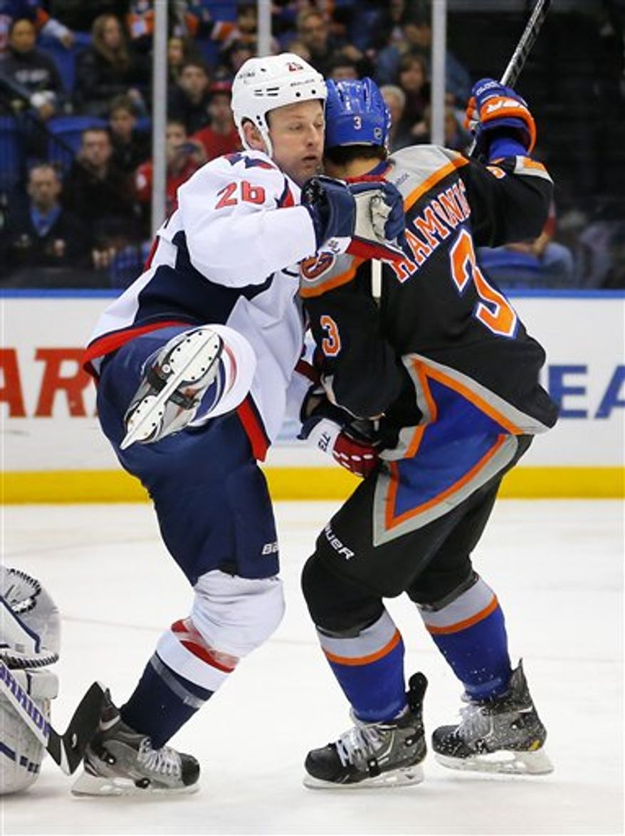 Washington Capitals center Matt Hendricks (26) is tied up by New York Islanders defenseman Travis Hamonic (3) in front of the Islanders net during an NHL hockey game at the Nassau Coliseum in Uniondale, N.Y., Saturday, March 9, 2013. (AP Photo/Paul J. Bereswill)