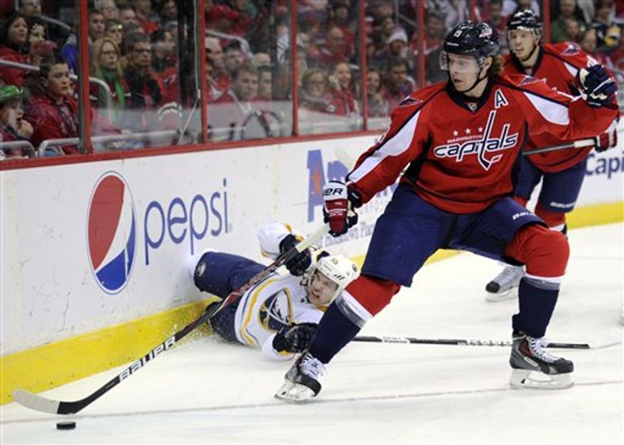 Washington Capitals center Nicklas Backstrom (19), of Sweden, reaches for the puck as Buffalo Sabres right wing Brian Flynn, left, falls to the ice during the first period of an NHL hockey game on Sunday, March 17, 2013, in Washington. (AP Photo/Nick Wass)