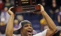 James Madison forward Rayshawn Goins holds the trophy after his team defeated Northeastern 70-57 at the Colonial Athletic Association Conference tournament championship NCAA college basketball game in Richmond, Va., Monday, March 11, 2013. (AP Photo/Steve Helber)