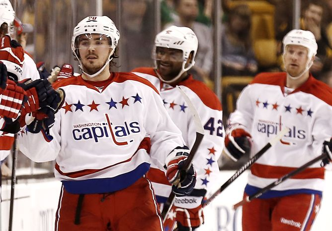 Washington Capitals' Marcus Johansson is congratulated at the bench after his goal during the second period of a NHL hockey game against the Boston Bruins in Boston Saturday, March 16, 2013. (AP Photo/Winslow Townson)