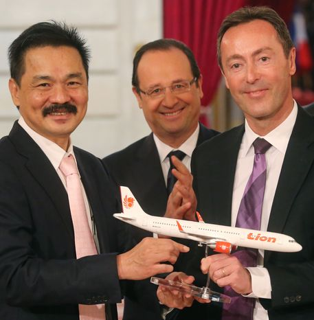 Rusdi Kirana (left), CEO of Lion Air, and Fabrice Bregier (right), CEO of Airbus, pose with an Airbus A320 model while French President Francois Hollande stands behind during a contract-signing ceremony at the Elysee Palace in Paris on Monday, March 18, 2013. Indonesian carrier Lion Air is to buy 234 short