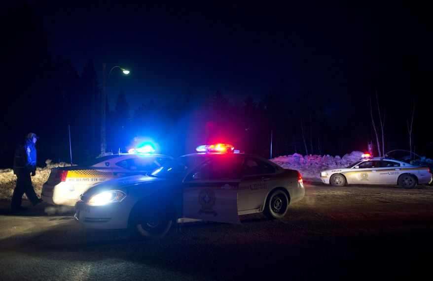 Police vehicles block a road just outside the town of Chertsey, Quebec, on March 17, 2013, during a search for escaped prisoners. A dramatic daylight jailbreak involving two inmates climbing a rope into a hovering helicopter swiftly escalated into a large police operation Sunday night in which at least one escapee was tracked down hours after he fled. (Associated Press/The Canadian Press)