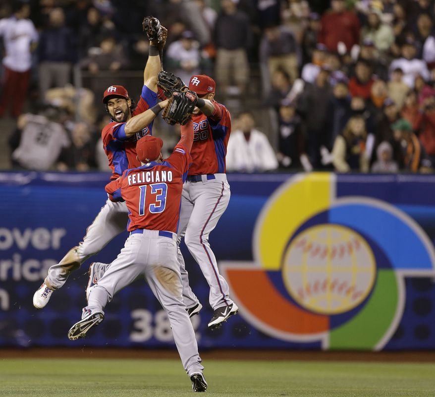 Puerto Rico's Angel Pagan, left, Jesus Feliciano (13) and Alex Rios celebrate after beating Japan 3-1 in a semifinal game of the World Baseball Classic in San Francisco, Sunday, March 17, 2013. (AP Photo/Eric Risberg)