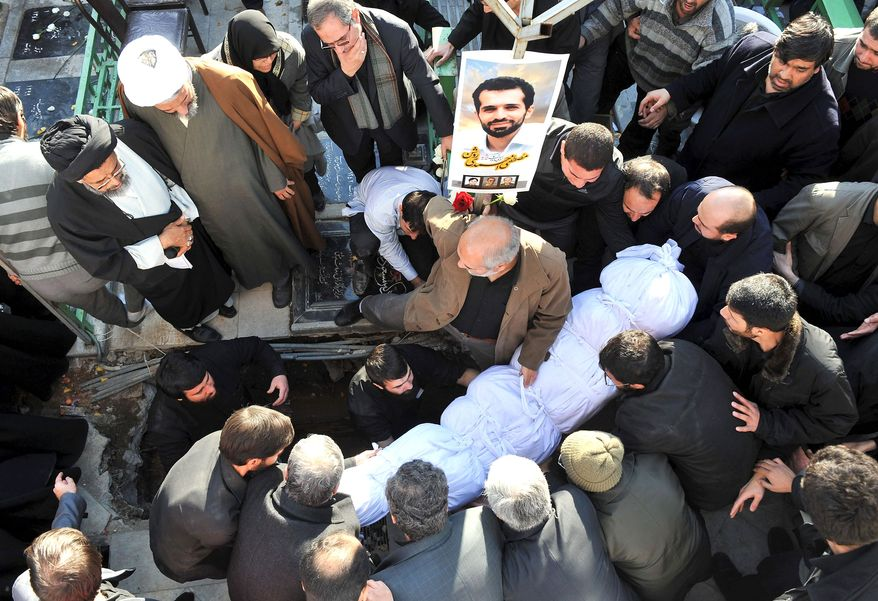 TARGETED: Mostafa Ahmadi Roshan, a chemistry specialist and a director of a uranium enrichment facility Iran, was killed in 2012 when a magnetic bomb was attached to his car and then exploded. A crowd surrounds his body. (Associated Press)