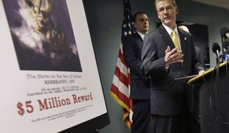 FBI Special Agent in Charge Richard DesLauriers (right) stands next to a poster that shows a Rembrandt painting and a reward during a news conference at FBI headquarters in Boston on Monday, March 18, 2013. The FBI believes it knows the identities of the thieves who stole artworks valued at up to $500 million from Boston's Isabella Stewart Gardner Museum more than two decades ago. Mr. DesLauriers says the thieves belong to a criminal organization based in New England and the Mid-Atlantic states. (AP Photo/Steven Senne)