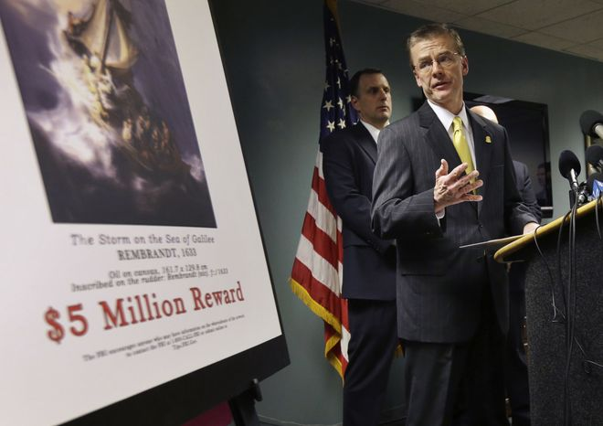 FBI Special Agent in Charge Richard DesLauriers (right) stands next to a poster that shows a Rembrandt painting and a reward during a news conference at FBI headquarters in Boston on Monday, March 18, 2013. The FBI believes it knows the identities of the thieves who stole artworks valued at up to $500 million from Boston's Isabella Stewart Gardner Museum more than two decades a