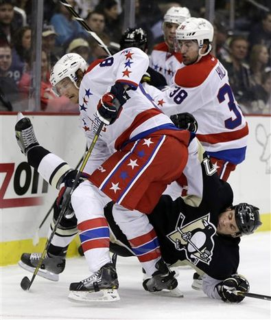 Pittsburgh Penguins right wing Craig Adams (27) collides with Washington Capitals center Jay Beagle (83) in the second period of an NHL hockey game in Pittsburgh Tuesday, March 19, 2013. (AP Photo/Gene J. Puskar)