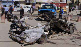 Iraqi security forces inspect the scene of a car bomb attack in the Shiite stronghold of Sadr City, Baghdad, Iraq, Tuesday, March 19, 2013. Insurgents unleashed deadly attacks Tuesday against Shiite areas of Baghdad, killing and wounding scores of people, police said. (AP Photo/Karim Kadim)