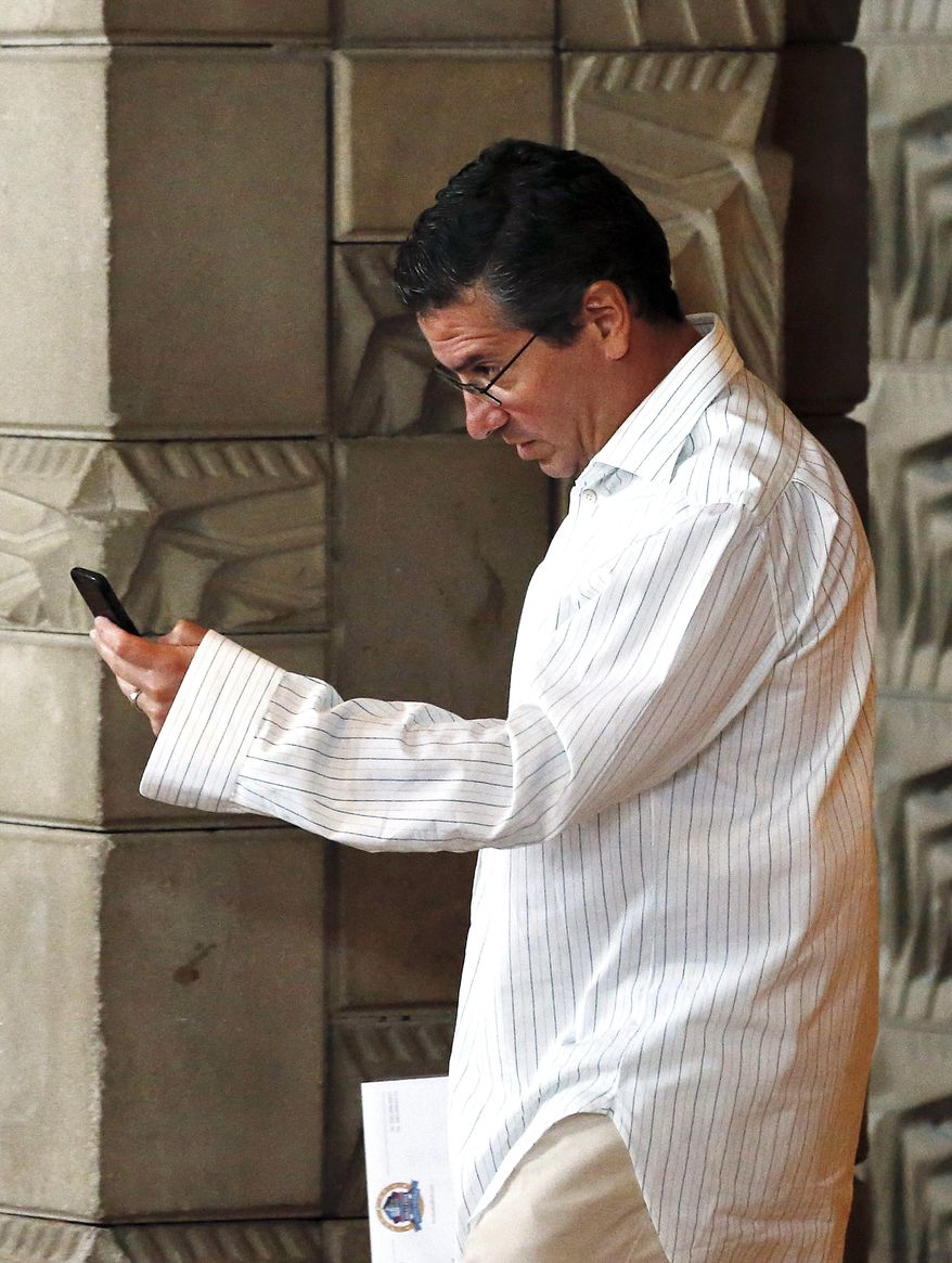 Washington Redskins owner Dan Snyder checks his phone after the morning session at the NFL football annual meetings at the Arizona Biltmore, Tuesday, March 19, 2013, in Phoenix. (AP Photo/Ross D. Franklin)
