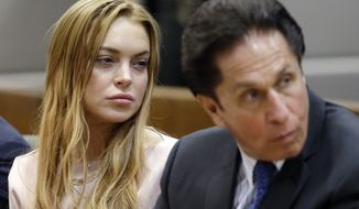 Actress Lindsay Lohan (left) and her attorney, Mark Heller, appear at a hearing in Los Angeles Superior Court on Monday, March 18, 2013. Miss Lohan accepted a plea deal in a misdemeanor car crash case that includes 90 days in a rehabilitation facility. (AP Photo/Reed Saxon, Pool)
