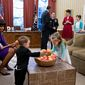 "First lady Michelle Obama and President Obama are shown during ""snack time"" in the Oval Office. The photo was tweeted by Obama's former campaign arm, now known as Organizing for Action."