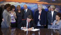 ** FILE ** Sponsors and family members of victims watch as Colorado Gov. John Hickenlooper signs gun-control bills into law at the Capitol in Denver on Wednesday, March 20, 2013. The bills, which place new restrictions on firearms, thrust Colorado into the national spotlight as a potential test of how far the country might be willing to go on new restrictions after the horror of the Newtown, Conn., and Aurora, Colo., shootings. (Associated Press)