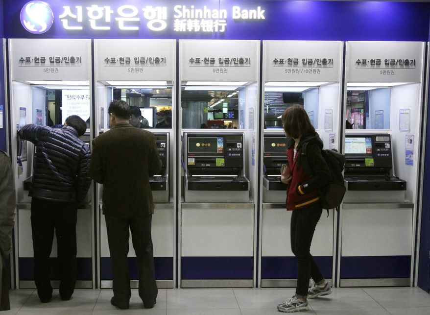 Depositors try to use automated teller machines of Shinhan Bank while the bank's computer networks are paralyzed at a subway station in Seoul, South Korea, Wednesday, March 20, 2013. (AP Photo/Ahn Young-joon)