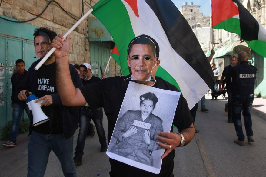 A Palestinian activist wearing a mask of U.S. President Obama holds a photo of Rosa Parks when she was arrested for refusing to give up her seat on a bus, in the West Bank town of Hebron on Wednesday, March 20, 2013. (AP Photo/Nasser Shiyoukhi)