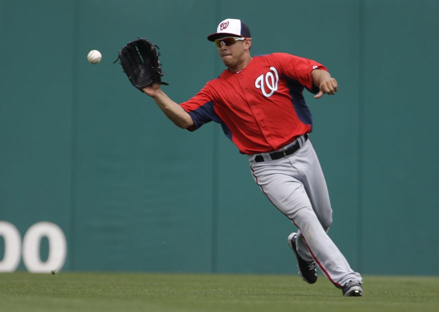 Washington Nationals center fielder Erik Komatsu handles the ball during the sixth inning of an exhibition spring training baseball game against the Miami Marlins Wednesday, March 20, 2013, in Jupiter, Fla. (AP Photo/Jeff Roberson)