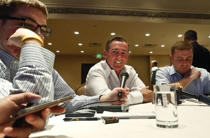 Washington Redskins head coach Mike Shanahan, center, smiles as he pauses before answering a question from the media during the NFC coaches breakfast at the annual NFL football meetings at the Arizona Biltmore, Wednesday, March 20, 2013, in Phoenix. (AP Photo/Ross D. Franklin)