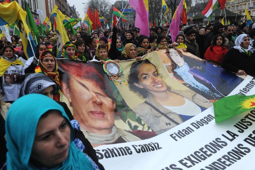 **FILE** Kurds march with flags and a banner showing pictures of the three PKK (Kurdistan Workers Party) activists killed in Paris last month to show support for them and to their leader Abdullah Ocalan, imprisoned in Turkey, during a Feb. 16 2013, protest in Strasbourg, France. Kurds from France, Germany and Belgium gathered for the march. (Associated Press)