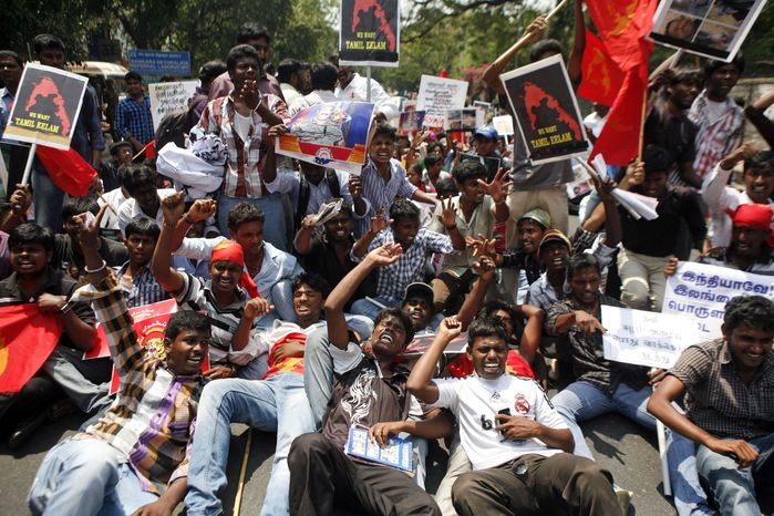 Indian Tamil activists and supporters lie on a road and shout slogans during a protest against Sri Lanka's alleged wartime abuses in Chennai, India, on March 21, 2013. A key ethnic Tamil party withdrew from India's coalition government Tuesday, accusing the government of watering down a U.N. resolution criticizing Sri Lanka's war-time conduct against its minority Tam