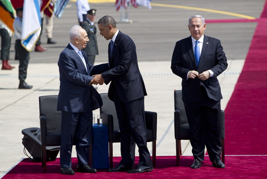 President Obama (center) and Israeli President Shimon Peres (left) shake hands as Israeli Prime Minister Benjamin Netanyahu looks on during a welcoming ceremony upon Mr. Obama's arrival at Ben Gurion Airport near Tel Aviv on Wednesday, March 20, 2013. (AP Photo/Ariel Schalit)