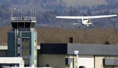 A small plane takes off past the control tower at Troutdale Airport in Troutdale, Ore., on March 7, 2013. (Associated Press)