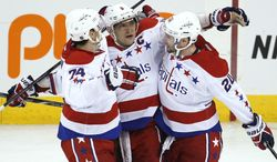 Washington Capitals' Alex Ovechkin (8), John Carlson (74) and Troy Brouwer (20) celebrate Ovechkin's goal against the Winnipeg Jets during the third period of an NHL hockey game in Winnipeg, Manitoba, on Thursday, March 21, 2013. The Capitals won 4-0. (AP Photo/The Canadian Press, John Woods)