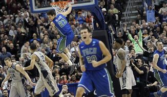 Florida Gulf Coast's Eddie Murray (23) hangs from the rim after a dunk as Chase Fieler (20) and Brett Comer (0) celebrate during the second half of a second-round game against Georgetown in the NCAA college basketball tournament on Friday, March 22, 2013, in Philadelphia. (AP Photo/Michael Perez)